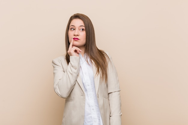 Young business woman looking sideways with doubtful and skeptical expression.