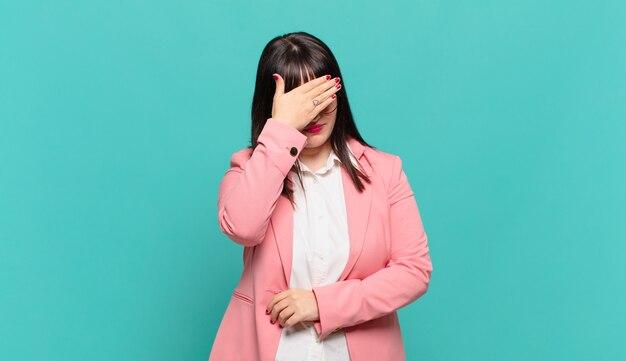 ストレス、恥ずかしがり屋、または動揺して、頭痛で、手で顔を覆っている若いビジネスウーマン