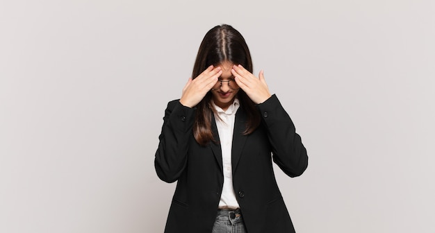 Young business woman looking stressed and frustrated, working under pressure with a headache and troubled with problems