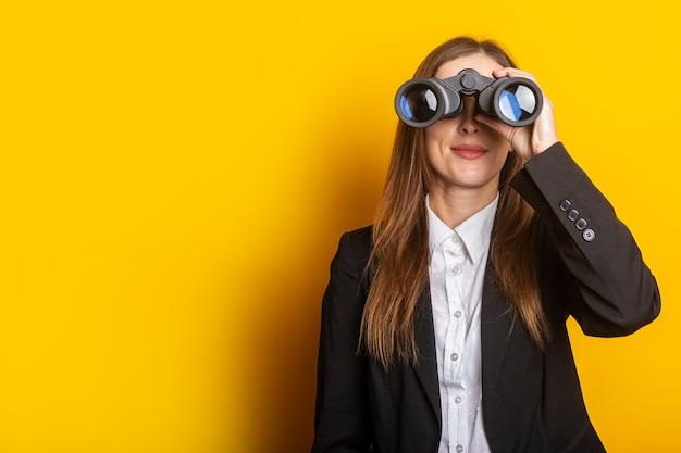 黄色の双眼鏡を通して見ている若いビジネス女性