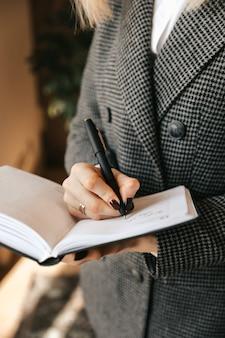 Молодая деловая женщина делает заметки в записной книжке в офисе.
