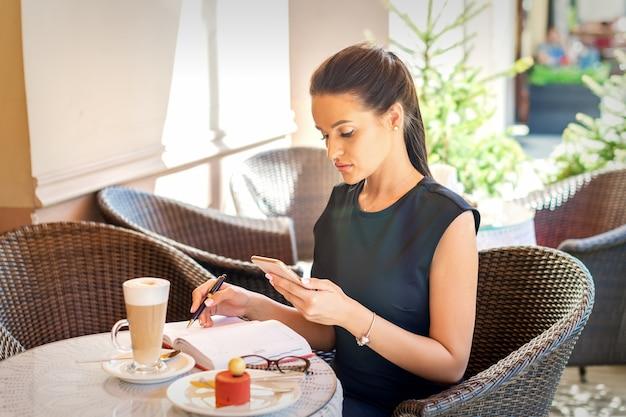 若いビジネスウーマンがカフェのコーヒーブレイクで働いているスマートフォンを見てノートにメモをとる