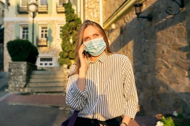 의료 보호 마스크를 쓴 젊은 비즈니스 여성 회사원은 도시 거리를 걷고 있는 스마트폰으로 이야기합니다. 라이프 스타일, 전염병의 비즈니스, 전염병, 나쁜 생태