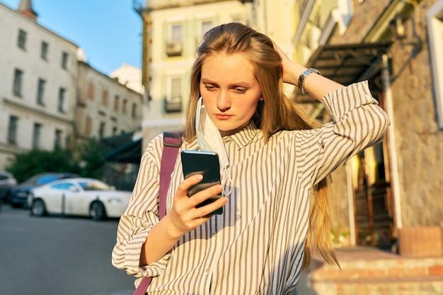 스마트폰을 손에 들고 의료용 보호 마스크를 쓴 젊은 비즈니스 여성 회사원, 귀가 열린 얼굴에 마스크. 도시의 거리에 여성입니다. 라이프 스타일, 전염병의 비즈니스, 전염병, 나쁜 생태