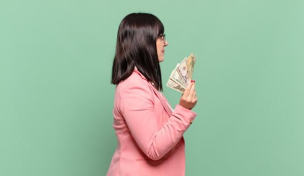 Молодая деловая женщина на виде профиля, желающая скопировать пространство впереди, думать, воображать или мечтать