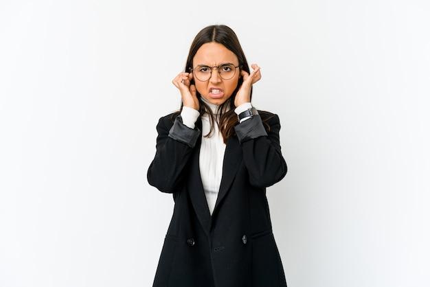Молодая бизнес-леди на белой стене покрывая уши с пальцами, усиленными и отчаянными громко окружающими.