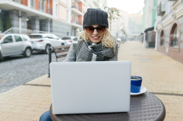 Young business woman in outdoor cafe with computer, mobile phone.