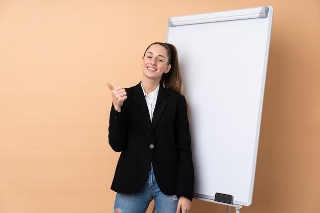 Молодая бизнес-леди над изолированной стеной давая представление на белой доске и с большими пальцами руки вверх