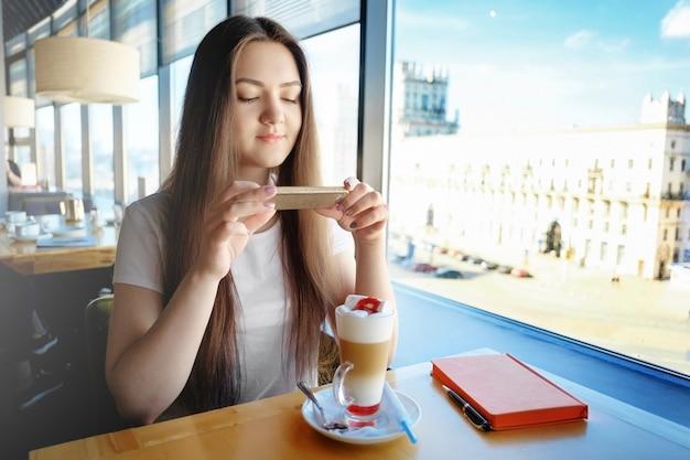 Молодая деловая женщина фотографирует своего красивого латте в кафе, социальные сети