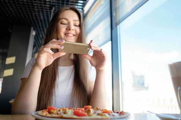 Молодая деловая женщина фотографирует свою красивую пиццу в кафе, социальные сети