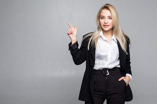 Young business woman pointing finger to the side on isolated grey wall