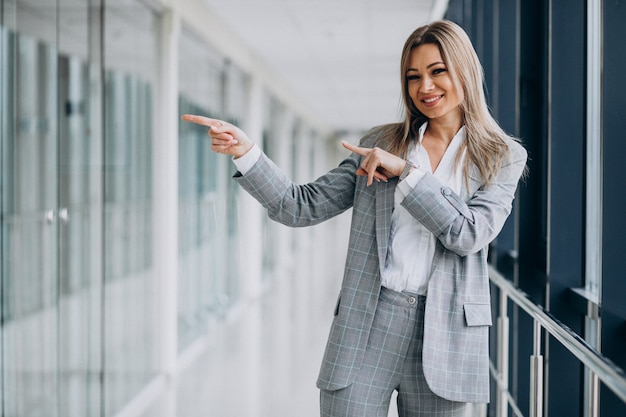 Young business woman pointing, in an office