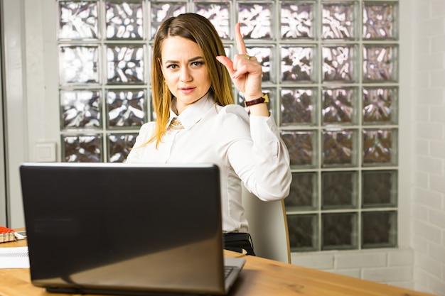 オフィスのデスクでアイデアを上向きにする若いビジネス女性