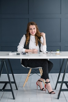 若いビジネス女性の肖像画。ワークスペースでプロの笑顔 Premium写真