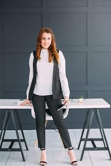 若いビジネス女性の肖像画。ワークスペースでプロの笑顔