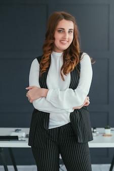 Портрет молодой бизнес-леди. улыбающийся профессионал на рабочем месте