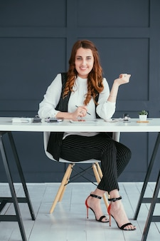 Young business woman portrait. smiling professional at workspace