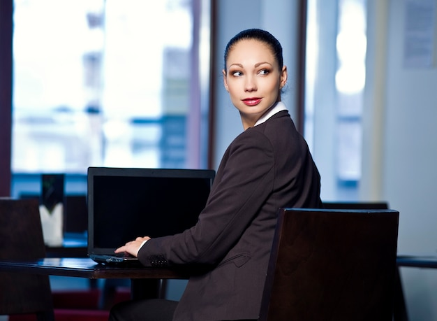 Young business woman poses on office background.