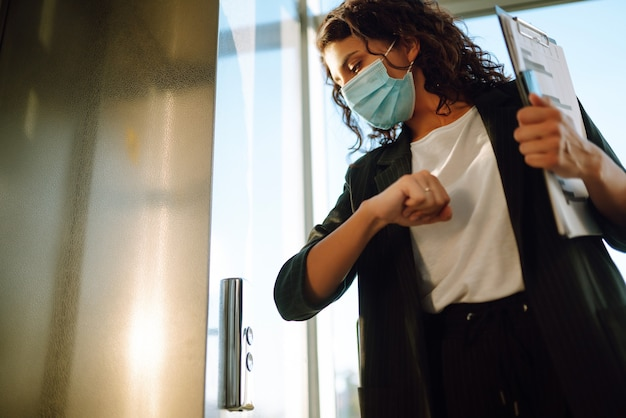 Young business woman in protective mask uses an elbow to press the elevator button.
