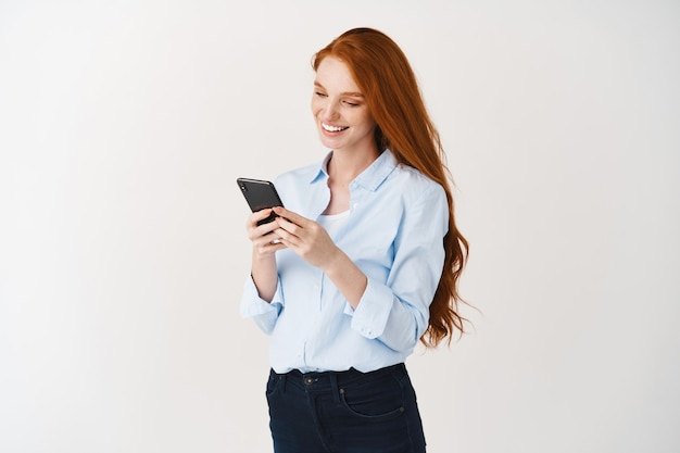 Young business woman reading message on smartphone and smiling, social networking while standing over white wall