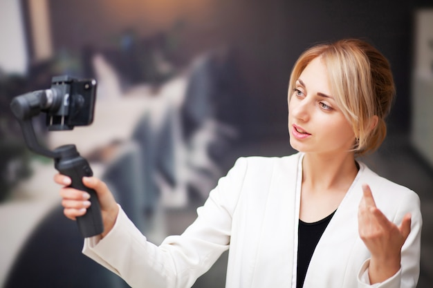 Young business woman recording video blog on smartphone in company office