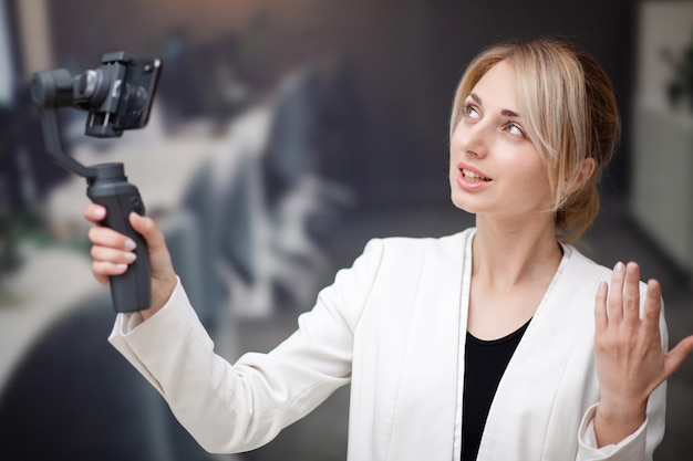 Young business woman recording video blog on smartphone in company office.