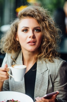 Young business woman resting in restaurant with cup of latte and dessert on table.