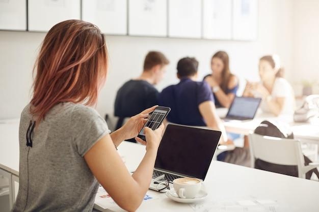 Молодая бизнес-леди, управляющая своим интернет-магазином с помощью портативного компьютера и смартфона в яркой студии или кафе. концепция предпринимателя.