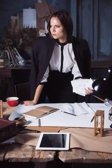 Young business woman scribbling documents at camera