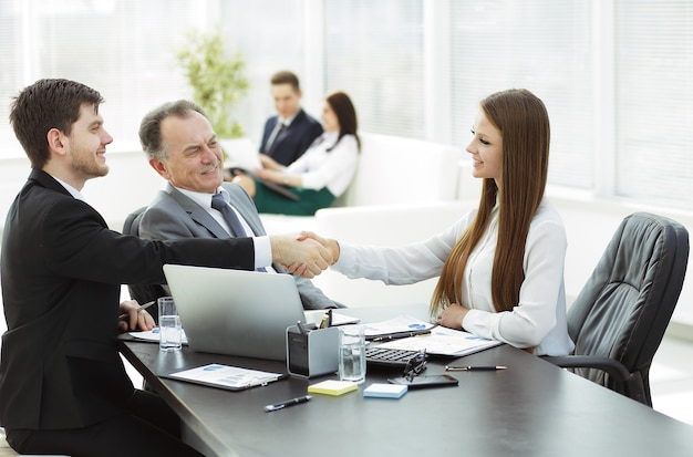 Young business woman shaking hands with an adult business partner.