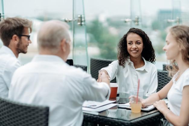 비즈니스 파트너와 악수하는 젊은 비즈니스 우먼