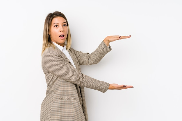 Young business woman shocked and amazed holding a copy space between hands.