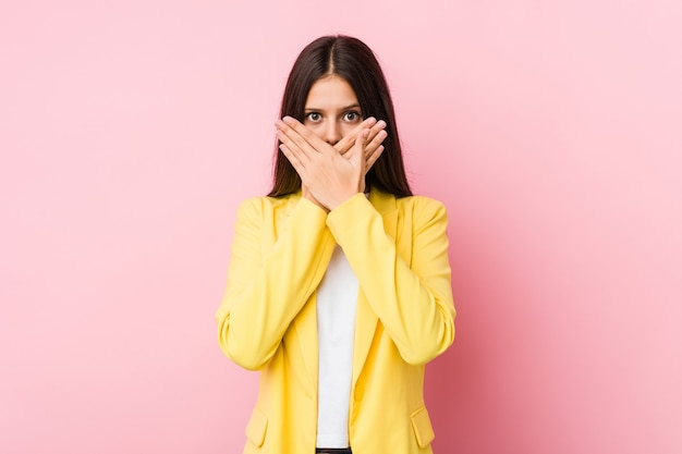 Молодая бизнес-леди потрясена прикрытием рта руками.