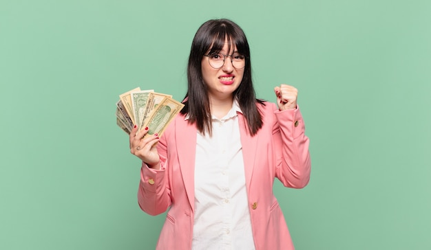 Young business woman shouting aggressively with an angry expression or with fists clenched celebrating success