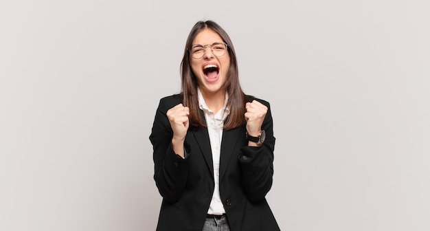 Young business woman shouting aggressively with annoyed, frustrated, angry look and tight fists, feeling furious