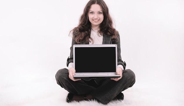 흰색에 floor.isolated에 앉아 노트북을 보여주는 젊은 비즈니스 우먼