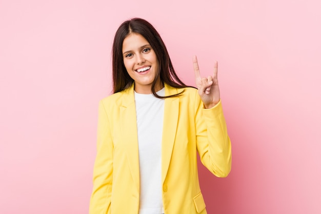 Young business woman showing a horns gesture as a revolution concept.