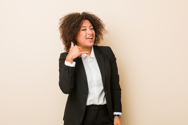 Young business woman showing a mobile phone call gesture with fingers.