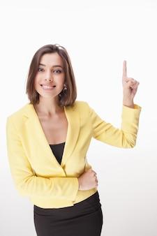白い背景の上に何かを示す若いビジネス女性