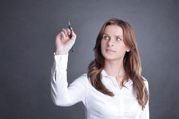Молодая деловая женщина, показаны карандашом на виртуальной точке. изолированные на темной стене.