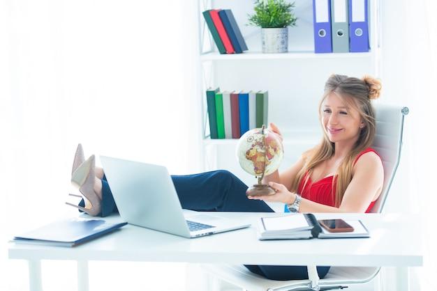 若いビジネスウーマンは、テーブルの上に足を持ってオフィスに座って、彼女の手で地球儀を持っています。休暇と旅行がしたいです。