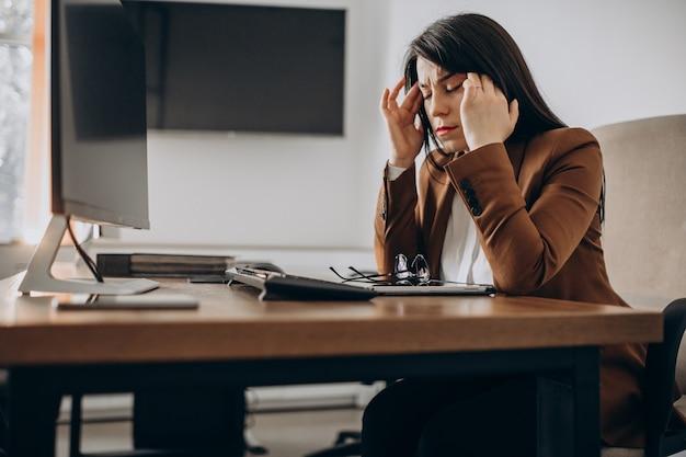 机に座って、コンピューターで作業している若いビジネス女性