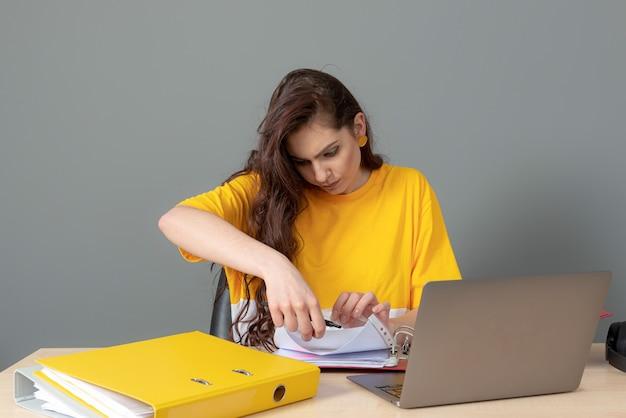 テーブルに座って、灰色の背景で隔離のドキュメントやラップトップで作業している若いビジネス女性