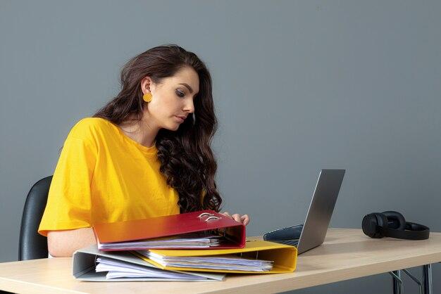 Молодая деловая женщина, сидящая за столом и работающая с документами и ноутбуком, изолированная на серой поверхности