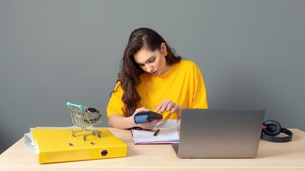 テーブルに座って、ドキュメントやラップトップで作業、灰色で隔離の若いビジネス女性