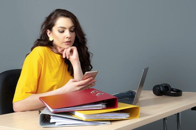 Молодая деловая женщина, сидящая за столом и работающая с документами и ноутбуком, изолированная на сером