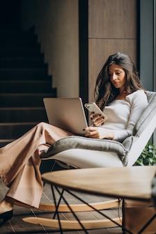 Giovane donna di affari che si siede in un cahir e che lavora al computer