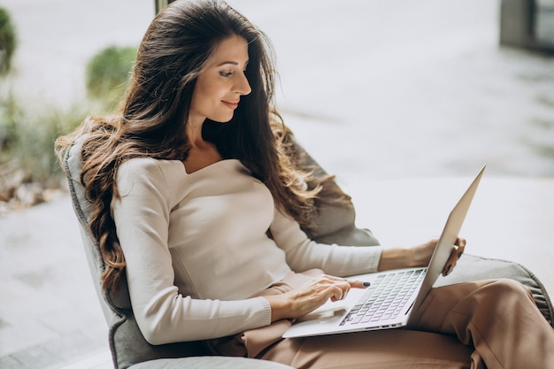 Young business woman sitting in a cahir and working on computer