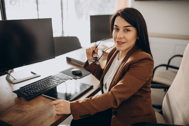 Young business woman sitting at desk and working on computer