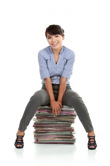 Young business woman sitting on document papers
